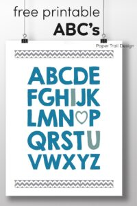 Wall art prints in blue with the complete ABC's with I, heart, and U written in a different colors suspended from clips with text overlay-free printable ABC's.