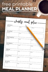 Meal planner on table with pencil and cup of coffee with text overlay- free printable meal planner