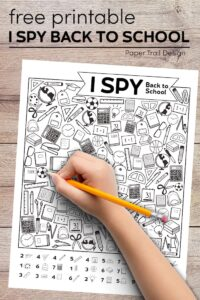 I spy printable page with kids hand holding a pencil with text overlay- free printable I spy back to school