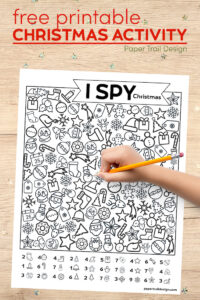Christmas themed I spy activity with kids hand holding pencil with text overlay- free printable Christmas activity
