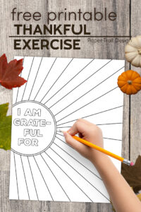 I am thankful for worksheet with kids hand holding pencil, leaves, and pumpkins with text overlay- free printable thankful exercise