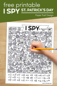 St. Patrick's Day themed I spy game with kids hand holding pencil with text overlay- free printable I spy St. Patrick's Day
