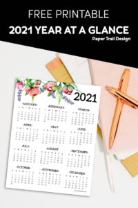 2021 one page calendar with floral elements lying on a stack of notebooks and a pen with text overlay- free printable 2021 year at a glance