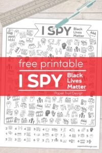 I spy Black Lives Matter themed activity page with pen and ruler laying over the top on a wood background with text overlay- free printable I spy Black Lives Matter