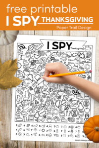 I spy Thanksgiving activity page with leaf, pumpkin, kids hand holding pencil with text overlay- free printable I spy Thanksgiving