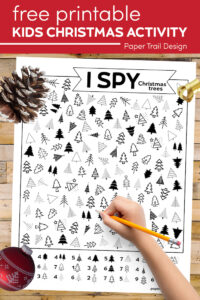 Christmas tree I spy page and kid's hand holding pencil with text overlay- free printable kids Christmas activity