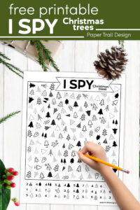 I spy Christmas tree game and kid's hand holding pencil with text overlay- free printable I spy Christmas trees