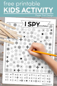 Kids snowflake I spy activity page with kids hand holding pencil with text overlay- free printable kids activity