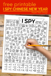 Chinese New Year game with kids hand holding pencil with text overlay- free printable I spy Chinese New Year
