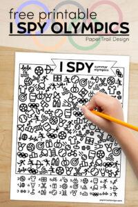 Summer Olympics themed I spy kids activity with kids hand holding pencil with text overlay- free printable I spy Olympics