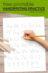 Kindergarten practice writing sheet with kids hand holding pencil with text overlay- free printable handwriting practice