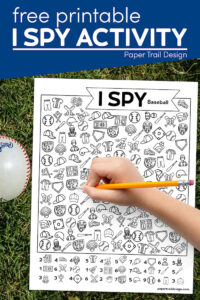 I spy baseball activity with kids hand holding pencil and a baseball in the grass with text overlay- free printable I spy activity