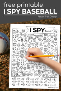 I spy baseball activity page with kid's hand holding pencil and a baseball in the dirt with text overlay- free printable I spy baseball