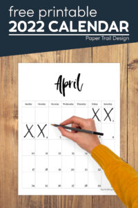 April calendar with hand holding pen crossing out days with text overlay- free printable 2022 calendar